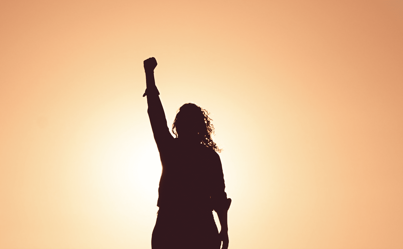 A silhouette of someone with their fist up.