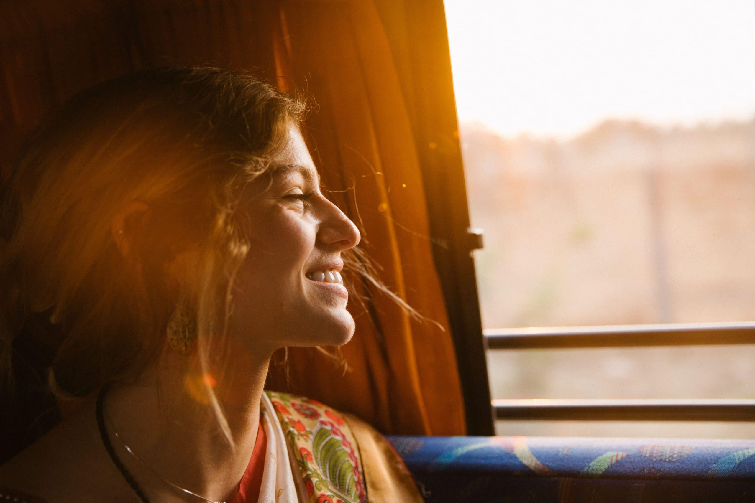 A lady smiling looking out a window.
