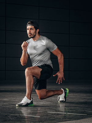 A man working his cardio by taking a lung step. Hitt doesn't involve any equipment just high circuit training.