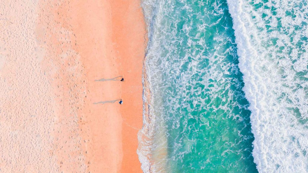 A horizontal beach aerial view with pink sand and bright blue and white waves crashing onto it.