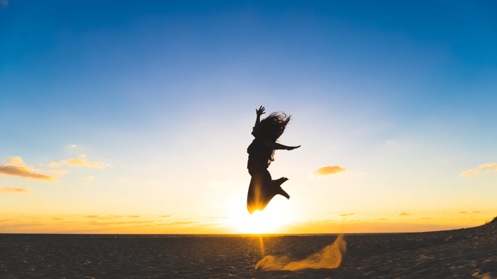 A woman jumps in front of a sunset.