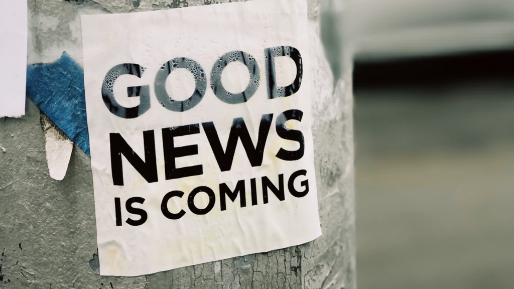"""A paper that reads, """"Good news is coming"""" hangs on a pole."""