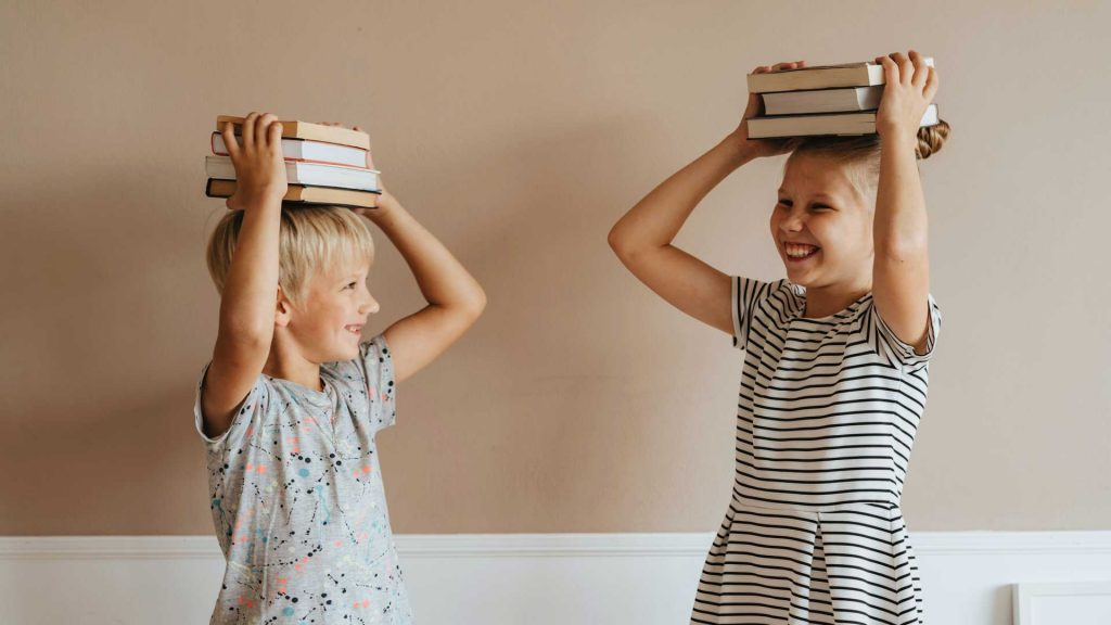 Two smiling children holding books above their heads. Soon to go over those books in the family book club.