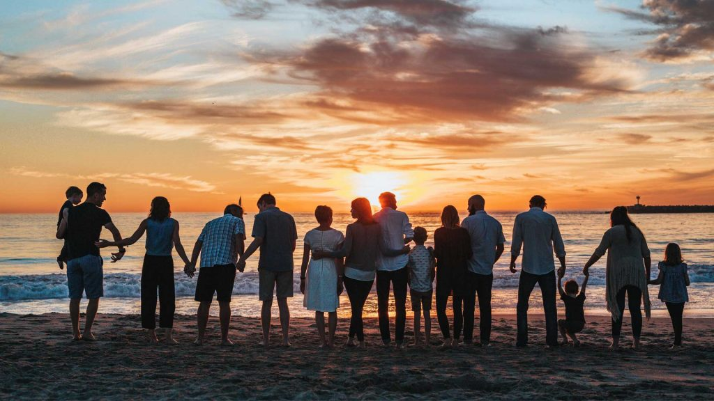 A big family group standing in a line holding hands with their backs to the camera. They are standing on a beach facing the sunset.