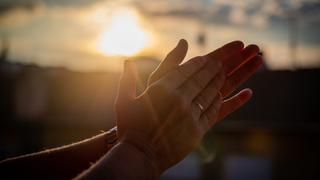A person claps their hands in front of the sunset.