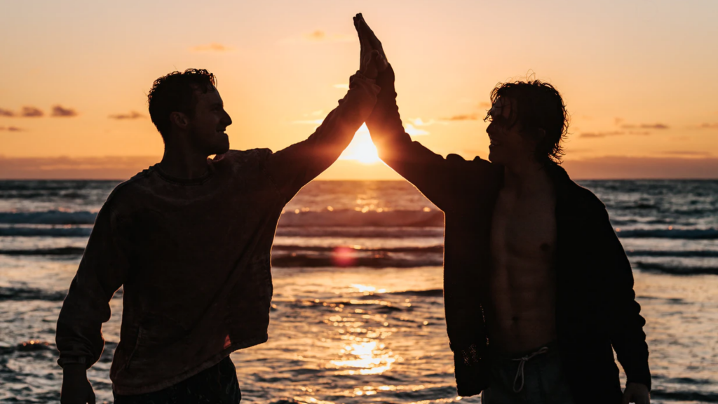 Two men high five in front of the beach at sunset.