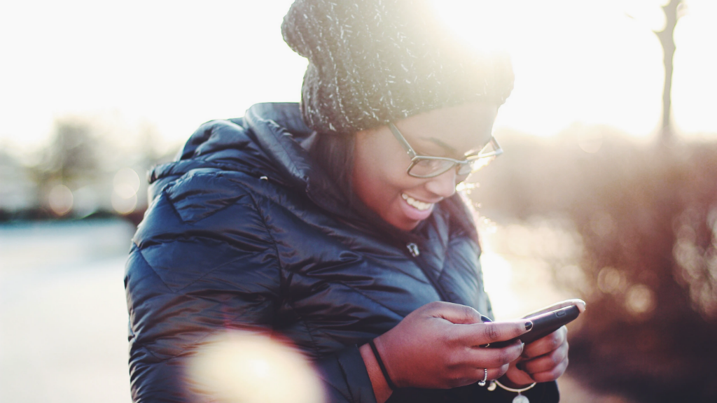 A woman smiles at her phone.