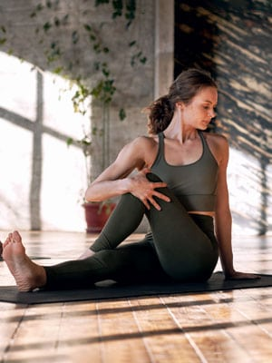 A woman wearing yoga clothing while stretching on her mat. Yin Yoga is a very relaxing, non-intense, stretching yoga.