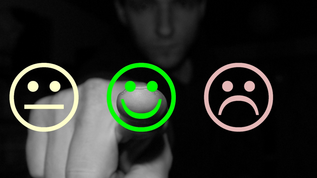 A man selects a smiling face with his finger over a sad and straight face.