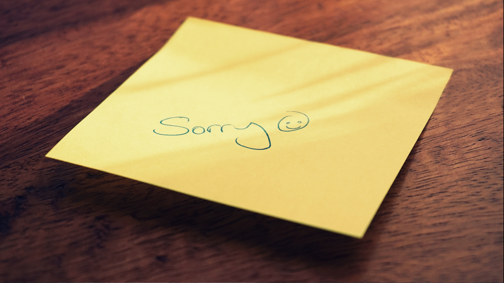 """A sticky note reads, """"Sorry"""" with a smiley face."""