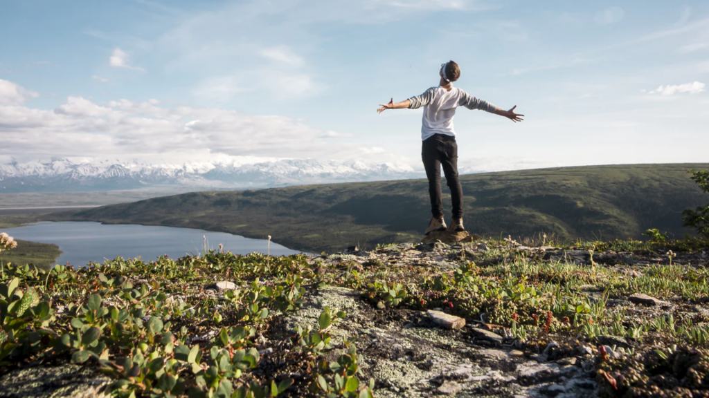 A man stands on a mountain with his arms open.