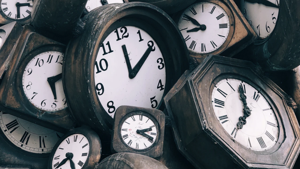 Clocks sit in a pile, reading different times.
