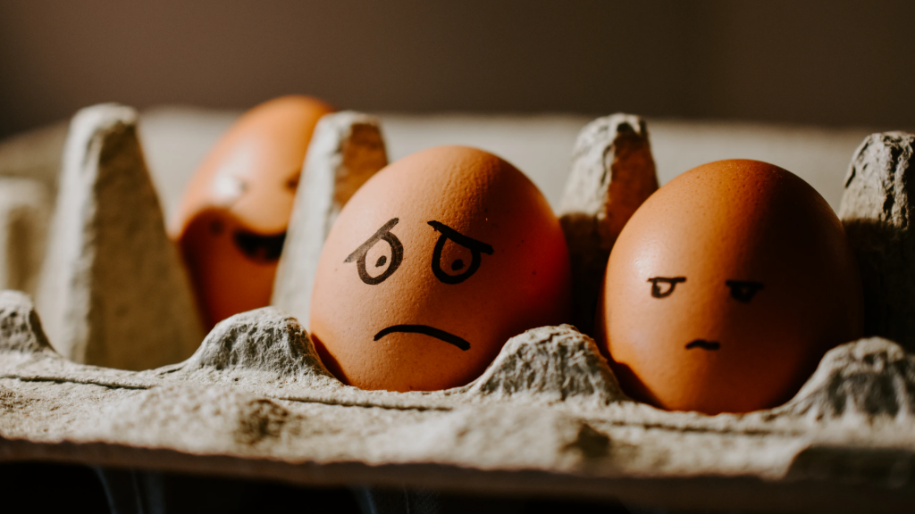 A brown egg has a worried face drawn on it, while the egg next to it has a mad face.