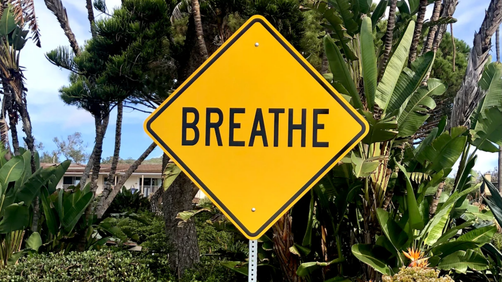 """A yellow traffic sign reads, """"Breathe."""""""