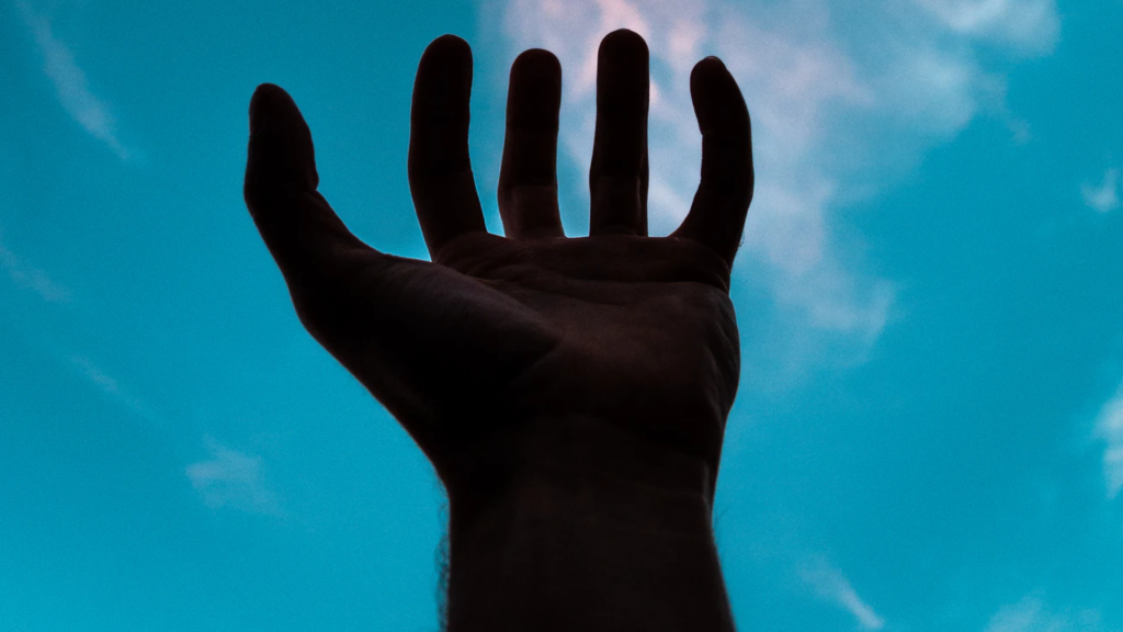 A hand is held up to the sky.