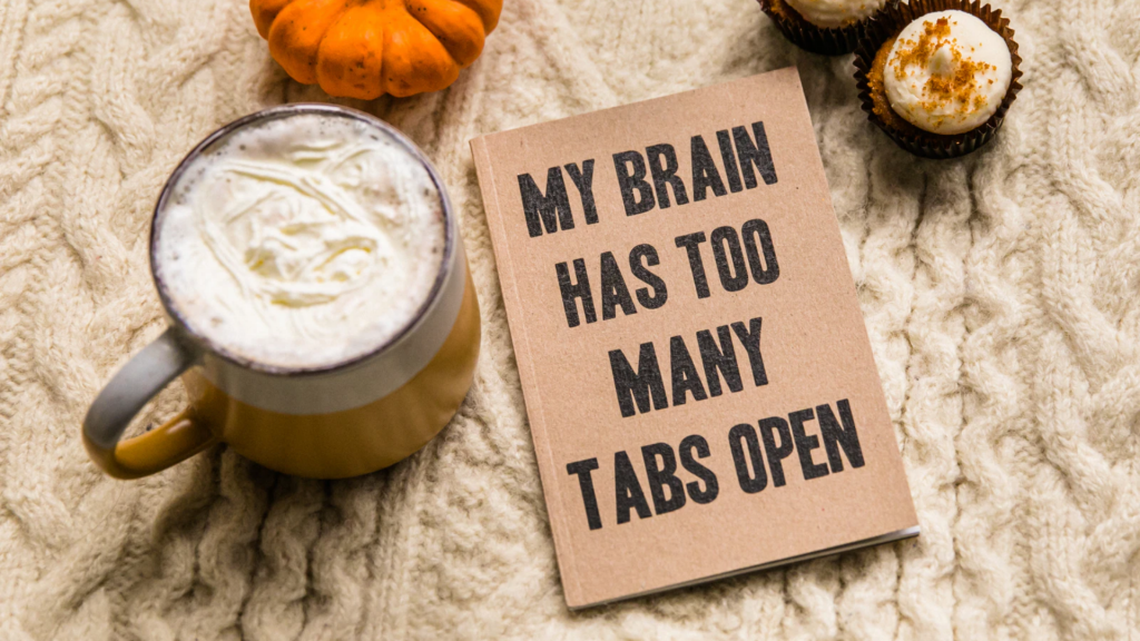 """A book that says, """"My Brain Has Too Many Tabs Open,"""" sits next to a cup of coffee and a cupcake."""